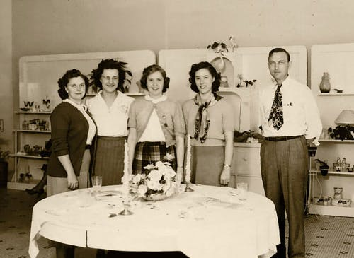 Busch's owner and four coworkers, gathered around a dining room centerpiece some time in the 1950s