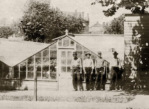 Four workers pose outside our original greenhouse in this undated 19th century photograph